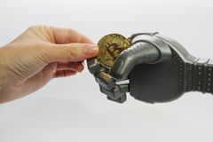 The man and the robot hold one gold coin - bitcoin royalty free stock photo