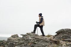 Man on rock admiring the view after a hike Stock Images