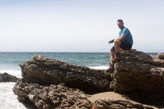 Man on a rock at the beach. Smiling Royalty Free Stock Photo