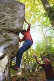 A man rock climber climbing a rock and his partner insuring. stock image