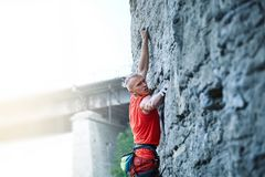 Rock climbing. man rock climber climbing the challenging route on the rocky wall. Man rock climber with long hair. close up side view of young man rock climber stock photos