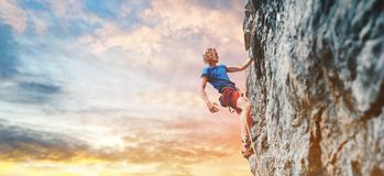 Male rock climber resting while climbing the challenging route on the rocky wall. Man rock climber with long hair. side view of young man rock climber in bright royalty free stock image