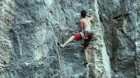 Man rock climber starting to climb on a cliff, searching, reaching and gripping hold.