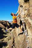 Man rock climbing a boulder. Side view of man in an orange shirt rock climbing a boulder Royalty Free Stock Photos