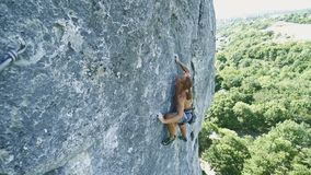 Man rock climbing on tough sport route, rock climber makes a hard move and falls.