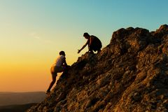 Free Man Rock Climbing With Another Man Helping Royalty Free Stock Photography - 110820667