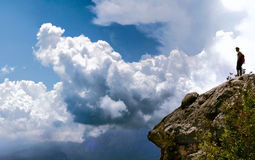 Man on rock in clouds. Man staying on a top of a rock in the clouds Royalty Free Stock Photo
