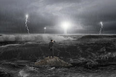 Man on rock gazing lighthouse in the ocean with storm. Man on rock gazing at lighthouse in the ocean with storm, thunder, lightering and waves in dark Stock Photography