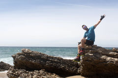 Man on a rock with his arms open Stock Images