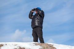 Man on the rock looking at binoculars Royalty Free Stock Image