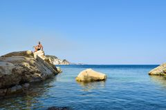 The man on the rock. The man on the rock in sea. Marathias beach, Zakynthos Island, Greece royalty free stock image