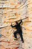 Man on rock wall in sport center Stock Photography