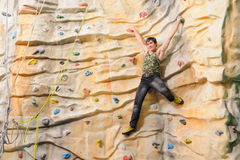 Man on rock wall in sport center Stock Photo