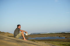 Man on Rocks with Book and Music. A man in his fourties sits on the rocks by the ocean with a book in his hand while watching the ocean and listening to some Royalty Free Stock Photos