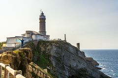 Man posing for a photo next to the lighthouse in Santander, Spain. Man on the rocks with open arms having fun and posing for a photo next to the lighthouse in stock image