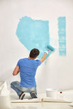 Man with roller painting wall in blue at home Royalty Free Stock Image