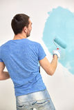 Man with roller painting wall in blue at home Royalty Free Stock Images