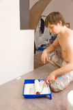 Man with roller and tray with paint Stock Photos
