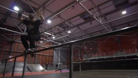 A man on rollers in a skate park performs a grind, in the background a person rides a bmx, slow motion. A sports man performs a trick with a pass on the railing stock footage