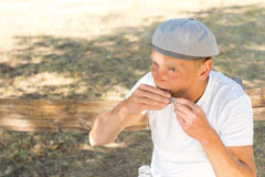 Man rolling a cigarette sealing the paper. Middle-aged man rolling a cigarette sealing the paper sitting on a bench in the park in a sunny day of summer Stock Photos
