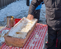 A man rolling hot maple taffy. A man rolling hot maple syrup on snow Stock Image
