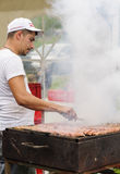 Man rolling mici on a large grill Stock Image