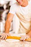 Man rolling out the dough. Royalty Free Stock Images