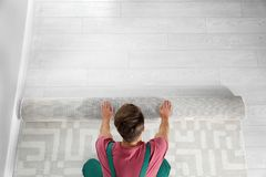 Free Man Rolling Out New Carpet Flooring Indoors, Top View. Royalty Free Stock Photography - 133307187