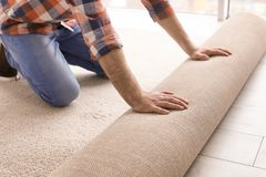 Man rolling out new carpet flooring. In room stock image