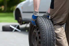 Man rolling a spare wheel Stock Images