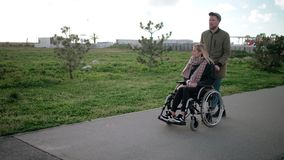 Man is rolling wheelchair with young blonde woman, walking together in park stock footage
