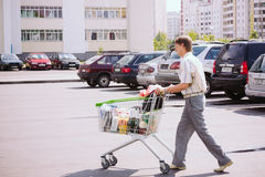 Man Rolls The Shopping Cart On The Parking Stock Photo