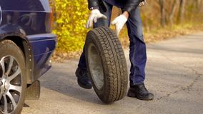 A man rolls a tire. Vertical view of rolling a spare of wheel stock video footage