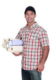 Man with rolls of wallpaper Royalty Free Stock Photography