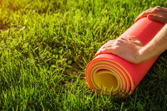 Man rolls yoga mat on the grass. At sunset royalty free stock photos