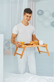 Man with romantic breakfast on tray Royalty Free Stock Images