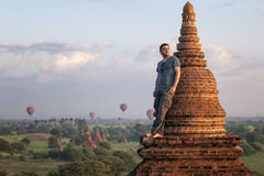 Man in a romantic pose standing on the roof against the backdrop of the city of Bagan and balloons royalty free stock image