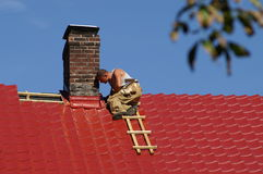 Man on the roof. Man working on the top of the roof Stock Photography