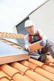 Man on roof checking installations Stock Images