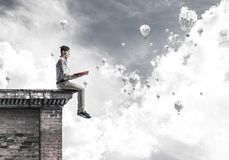 Man on roof edge reading book and aerostats flying in sky Stock Photography