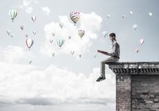Man on roof edge reading book and aerostats flying in sky Royalty Free Stock Photography