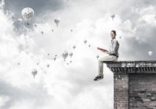 Man on roof edge reading book and aerostats flying in sky. Young shocked man or student sitting on building top with red book in hands Stock Photo