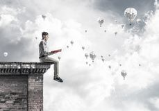 Man on roof edge reading book and aerostats flying in sky. Young shocked man or student sitting on building top with red book in hands Royalty Free Stock Photo