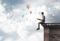 Man on roof edge reading book and aerostats flying in sky Royalty Free Stock Image