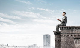 Man on roof edge reading book and cityscape at background Royalty Free Stock Images