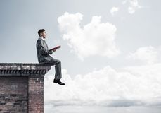 Man on roof edge reading book and cloudscape at background Stock Photos