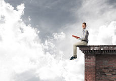 Man on roof edge reading book and cloudscape at background Royalty Free Stock Photography