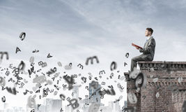 Man on roof edge reading book and symbols flying around Royalty Free Stock Image
