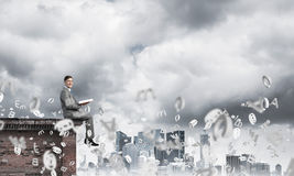 Man on roof edge reading book and symbols flying around Royalty Free Stock Photo