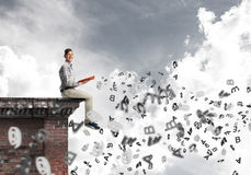 Man on roof edge reading book and symbols flying around. Young man in casual sitting on building edge with red book in hands Stock Image
